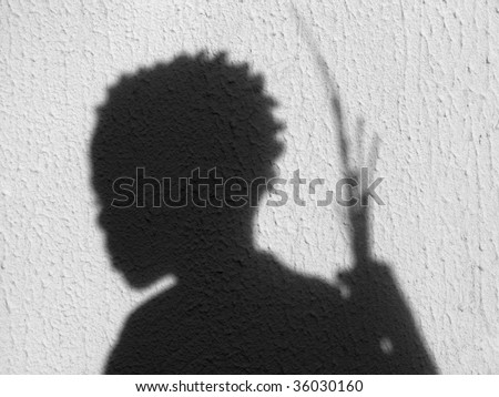 a boy's shadow against a textured wall - stock photo