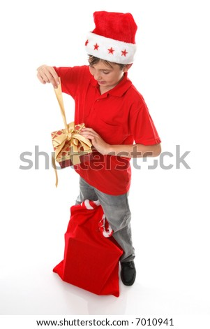 A boy, sack of toys at his feet,  opens a Christmas  present