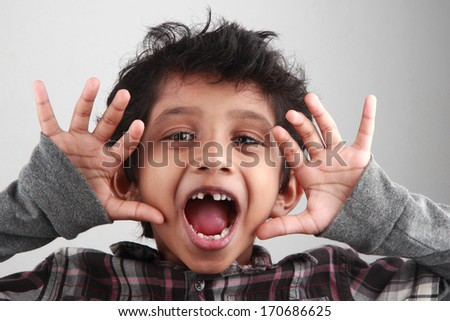 A boy screams with his mouth open - stock photo