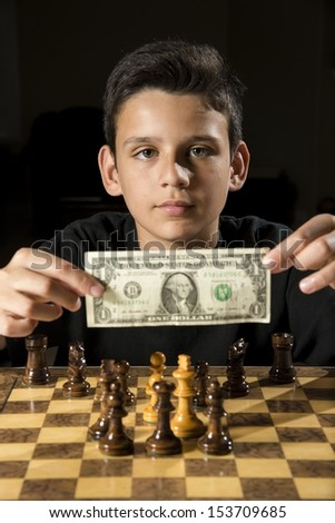 a boy shows money as he tries to bet on a chess game.  - stock photo