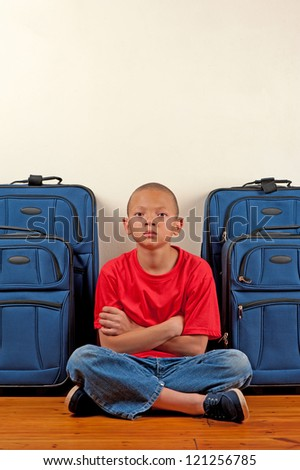 A boy sitting in front of suitcases appears upset. - stock photo