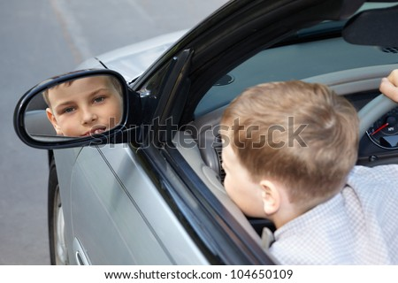 A boy, sitting on a driver place in an open top car, looks into the rear view mirror