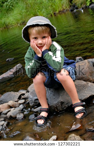 A boy sitting on a rock getting his feet wet in water - stock photo