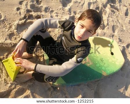 a boy sitting on his bodyboard board - stock photo