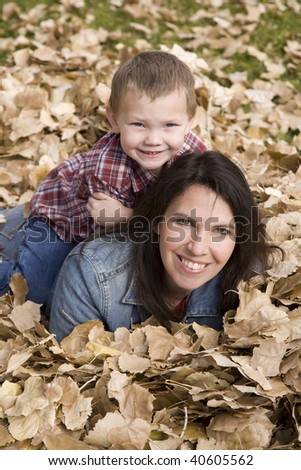 A boy sitting on his mothers back in the leaves.