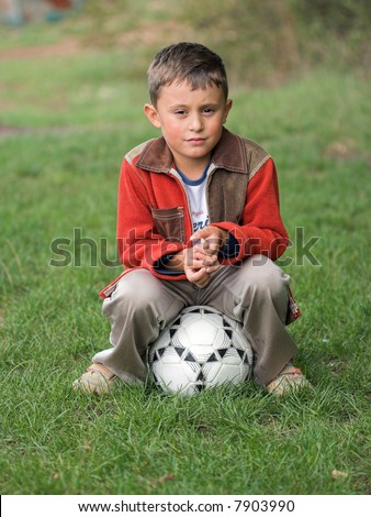 A boy sitting on soccer ball - stock photo
