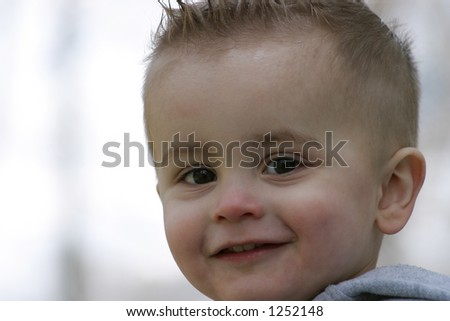 a boy smiling to the right side of the frame - stock photo