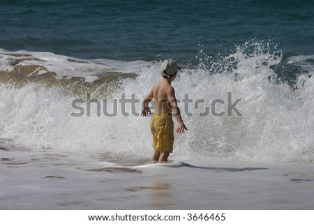 A boy standing and playing in the ocean. - stock photo