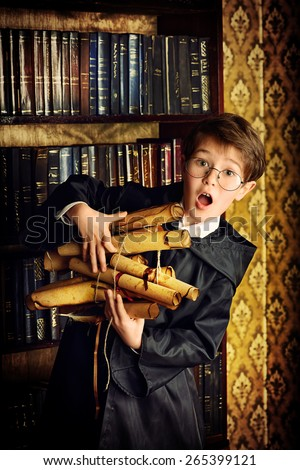 A boy stands in the library by the bookshelves with many old books and holds old manuscripts. Educational concept. Science. Vintage style. - stock photo