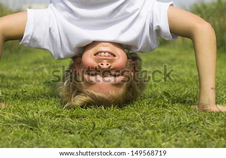 A boy stands upside down in the summer grass. - stock photo