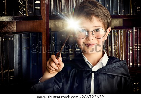 A boy stands with magic wand in the library by the bookshelves with many old books. Fairy tales. Vintage style. - stock photo