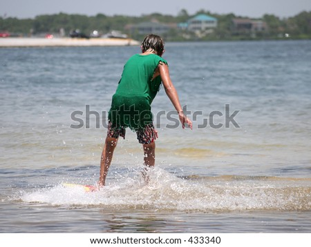 A boy surfing at the beach. - stock photo