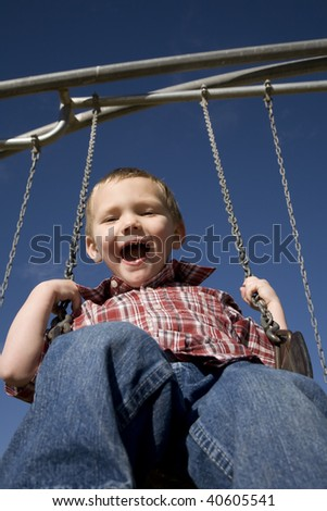 A boy swinging high up in the blue sky. - stock photo