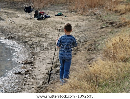 A boy walks along the shoreline of a rural lake with his fishing pole - stock photo