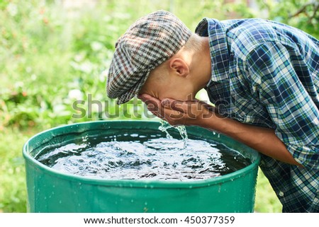 A boy washes his face in the water barrel on the farm