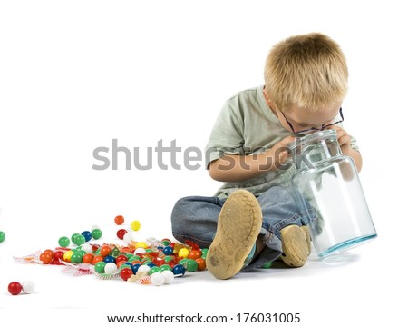 A boy wearing glasses and looking into an empty jar.