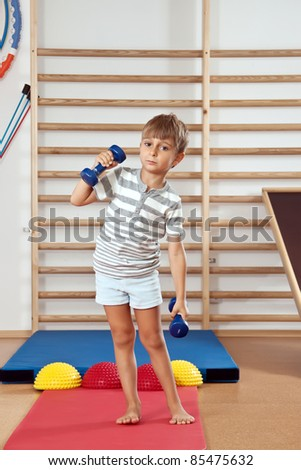 A boy with a dumbbell in the gym.