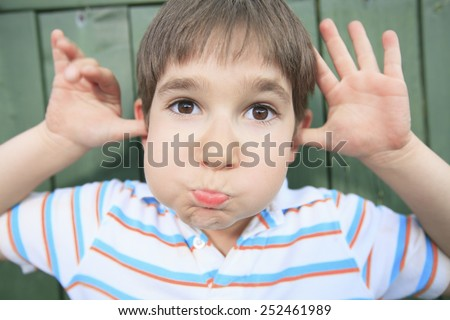 A boy with a funny face expression - stock photo