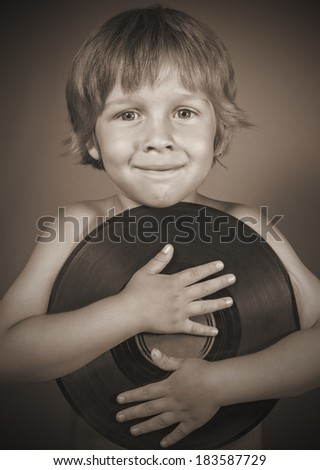 A boy with a record smiles - stock photo