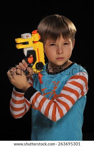 A boy with a toy gun depicts a special agent. - stock photo