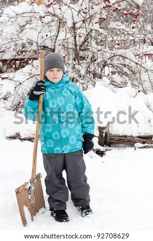A boy with a wooden shovel for snow removal - stock photo