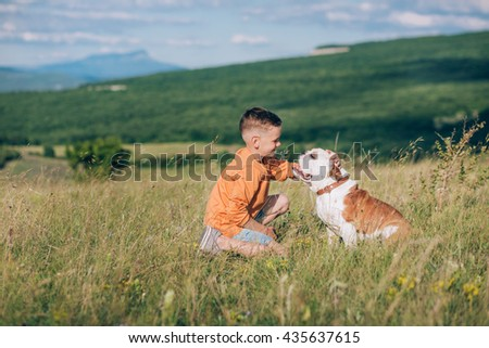 A boy with an english bulldog on a field. - stock photo