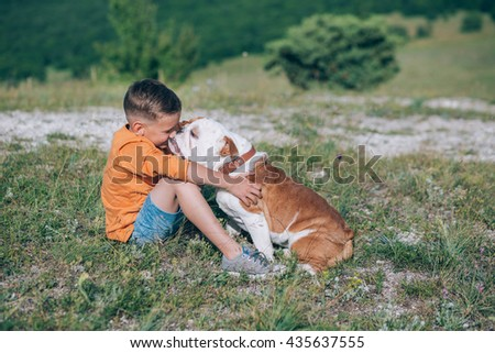 A boy with an english bulldog on a field. The Boy hugging his dog - stock photo
