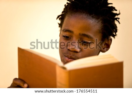 A boy with curly hair reads a book. - stock photo