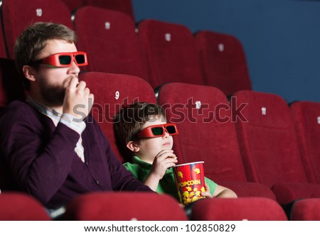 A boy with father eating popcorn in 3D movie theater - stock photo