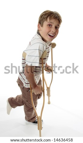 A boy with sprained injured ankle using crutches for support.  He is looking up and smiling. For healthcare and insurance themes - stock photo