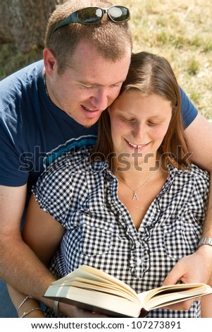 A boyfriend and girlfriend reading a book in a park - stock photo
