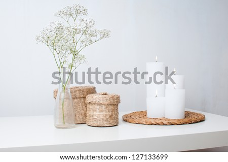A branch of flowers in a small vase, white candles on the stand and two closed baskets on a white table in an interior - stock photo