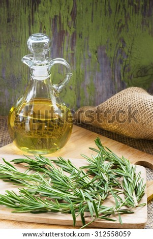 A branch of rosemary and bottle of olive oil on a cutting board in a old wooden background.