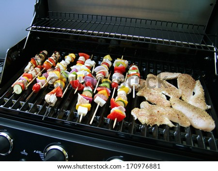 a brand new grill with meat and vegetables on it - stock photo