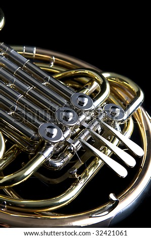 A brass and copper French horn isolated against a black background close up in the vertical format. - stock photo