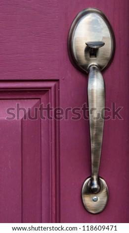A Brass Door Handle on a bright red door - stock photo