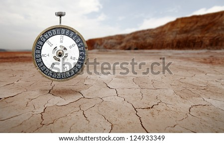A brass mechanical antique date watch floating in a surreal barren landscape for the concept of counting down to the end of the world due to global warming. - stock photo