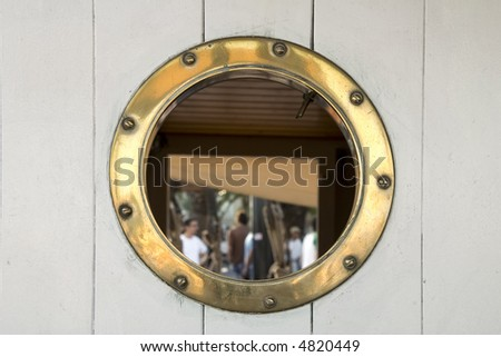 A brass porthole on a sailing boat - stock photo