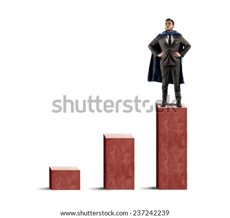 A brave businessman hero above the statistic - stock photo