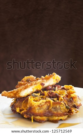 A breakfast of bacon-cheddar waffles with fried chicken and golden syrup, on a white plate, with a mottled brown background.