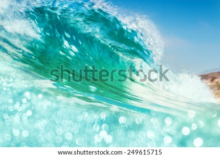 A breaking ocean wave with bright bokeh in the foreground.  Image made with subtle panning motion combined with a slow shutter speed for a soft blurring effect. - stock photo