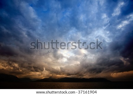 A brewing storm on an ocean sunset - stock photo