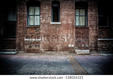 A brick alleyway with concrete walkway. Old windows and doors made of metal and glass with stairs and steps - stock photo