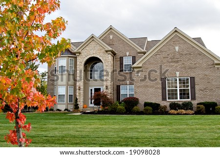 A brick and stone suburban home - nice landscaping. - stock photo