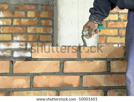 A brick layer putting down another row of bricks - stock photo