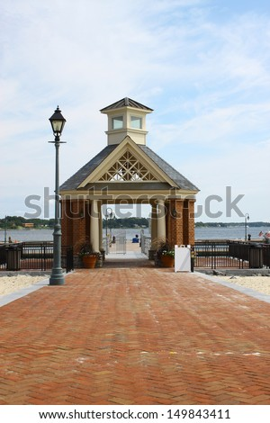 A brick walkway through a large Gazebo leading to the waterfront pier and boat dock landing along the riverwalk landing in Yorktown Virginia - stock photo