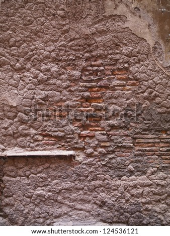 A brick wall covered with cement that is now wearing down - stock photo