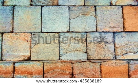 a brick wall made from concrete with orange and blue colors - stock photo