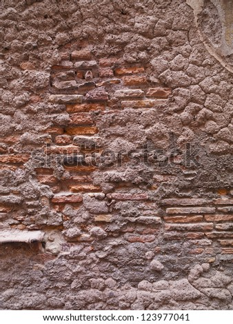 A brick wall with cement stuck onto it - stock photo