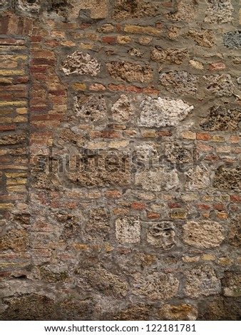 A brick wall with large stones also set into it - stock photo